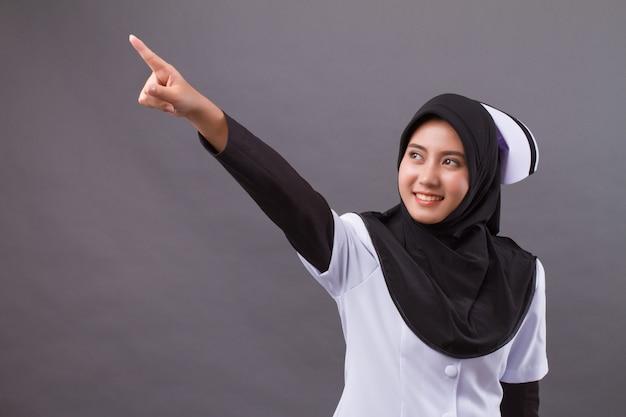 Enfermeira muçulmana apontando dedo para cima