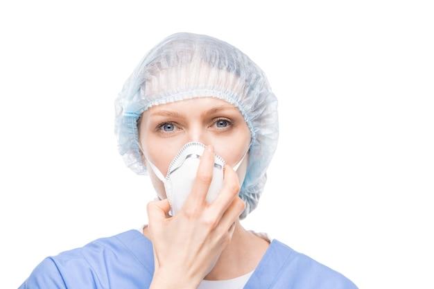 Enfermeira muito jovem com uniforme azul e lenço na cabeça segurando um respirador protetor perto do nariz enquanto fica em frente à câmera