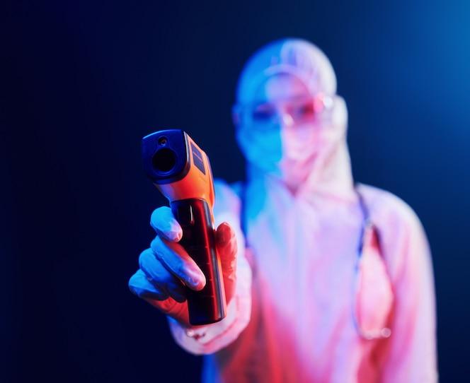Enfermeira na máscara e uniforme branco em pé na sala iluminada de néon e segurando o termômetro infravermelho. pare a disseminação do coronavírus