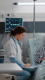 Enfermeira negra verificando os sinais vitais do paciente, monitorando a frequência cardíaca, injetando vitamina em uma bolsa coletora de fluidos iv na enfermaria do hospital