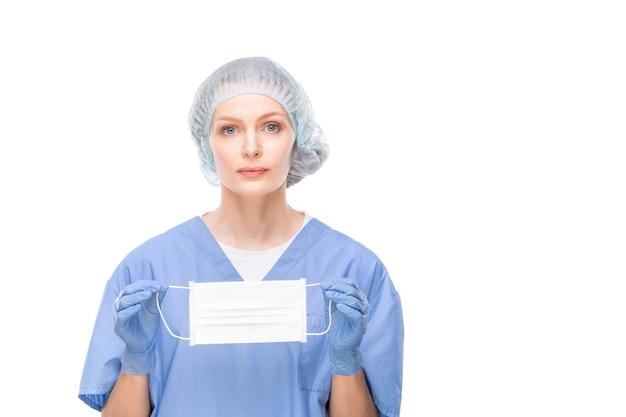 Enfermeira ou cirurgiã muito jovem em uniforme azul, luvas e lenço de cabeça segurando uma máscara protetora na frente de si mesma enquanto permanece isolada