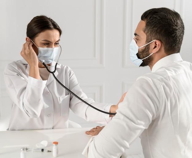 Enfermeira ouvindo batimentos cardíacos do homem