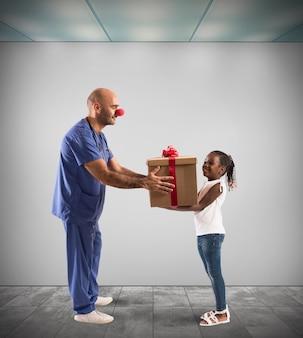 Enfermeira palhaço fazendo presente para uma criança