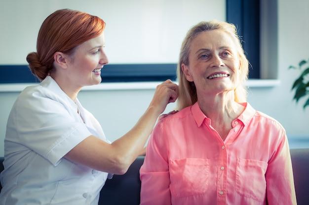 Enfermeira, penteando o cabelo da mulher sênior