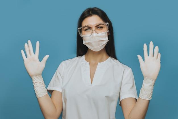 Enfermeira positiva usando óculos de proteção, uma máscara cirúrgica e um vestido médico mostra suas mãos.