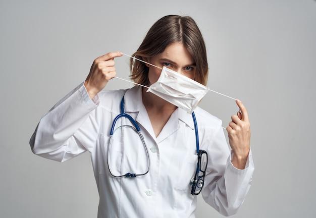 Enfermeira profissional com uma bata com um estetoscópio e uma máscara médica