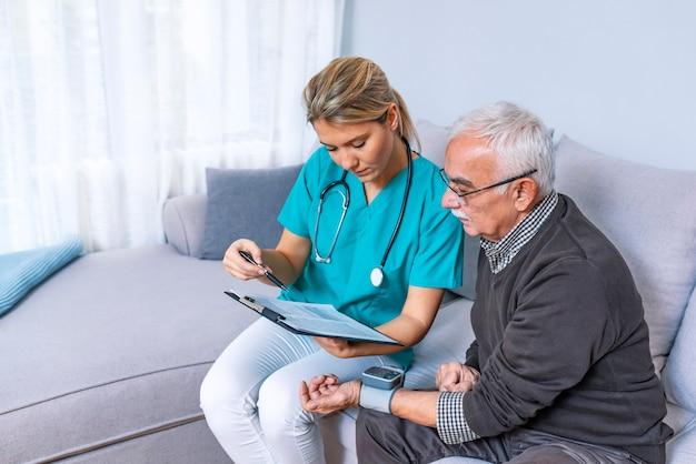 Enfermeira que faz a monitoração da pressão sanguínea para o homem superior em casa.
