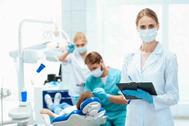 Enfermeira que levanta de encontro ao fundo do dentista que trata a menina.