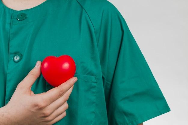 Enfermeira que prende o coração de plástico