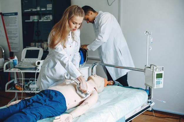 Enfermeira realiza reanimação. o médico ajuda a mulher a realizar a operação. os alunos praticam medicina.