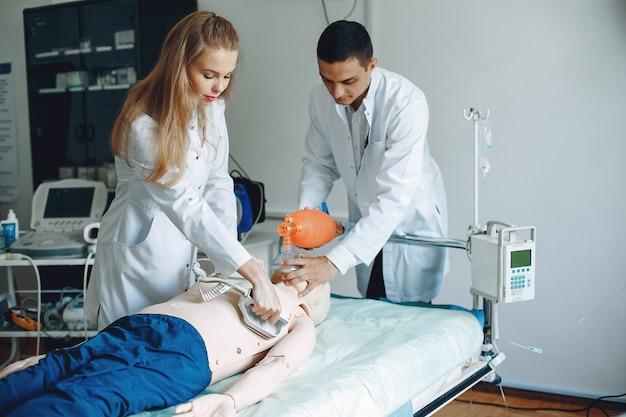 Enfermeira realiza reanimação. o médico ajuda a mulher a realizar a operação.