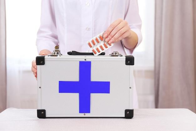 Enfermeira segurando kit de primeiros socorros no quarto