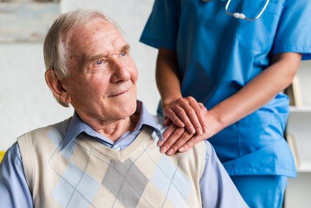 Enfermeira segurando o ombro do velho