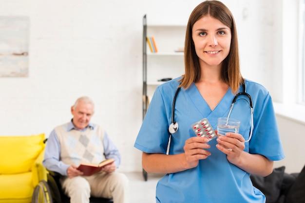 Enfermeira, segurando, pílulas, e, vidro água