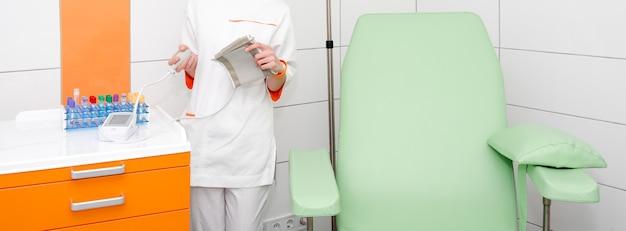 Enfermeira segurando um medidor digital de pressão arterial em um quarto de hospital moderno
