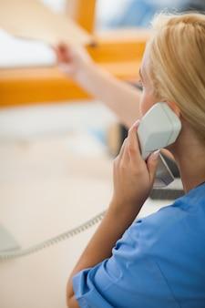 Enfermeira segurando um telefone e dando uma pasta