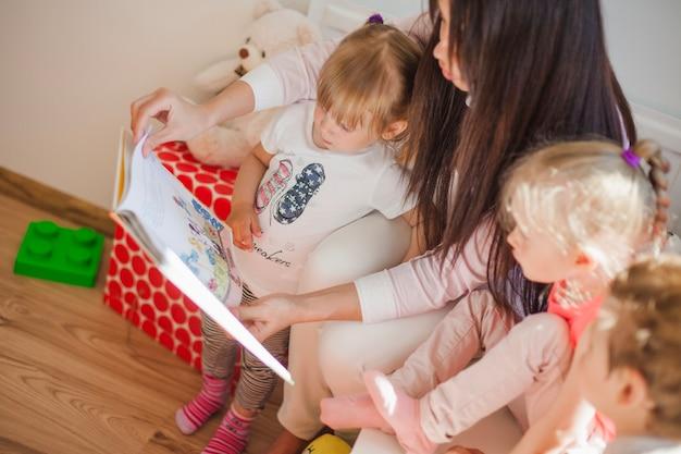 Enfermeira sentada com crianças e livro de leitura