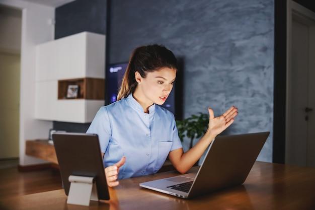 Enfermeira sentada em casa dando conselhos online
