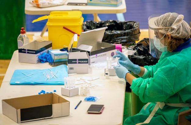 Enfermeira sentada manipulando diferentes suprimentos de enfermagem