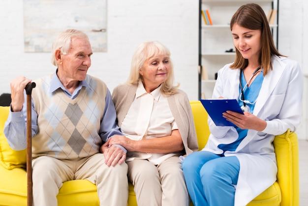 Enfermeira, sentando, com, homem velho, e, mulher, ligado, sofá