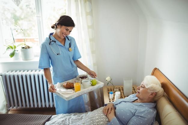 Enfermeira servindo café da manhã para mulher sênior