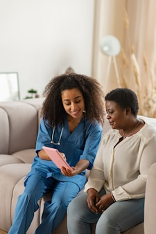 Enfermeira simpática. simpática enfermeira encaracolada de uniforme azul, mostrando notícias online para uma senhora afro-americana idosa