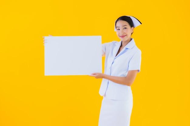 Enfermeira tailandesa de bela jovem mulher asiática retrato com quadro branco vazio