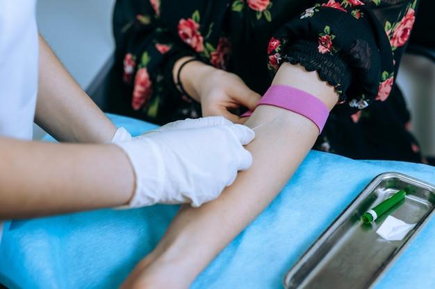Enfermeira tirando amostra de sangue do paciente no consultório médico