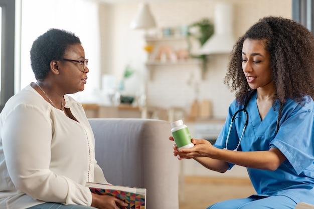 Enfermeira trazendo comprimidos. mulher idosa de pele escura com cabelo curto falando com a enfermeira trazendo comprimidos