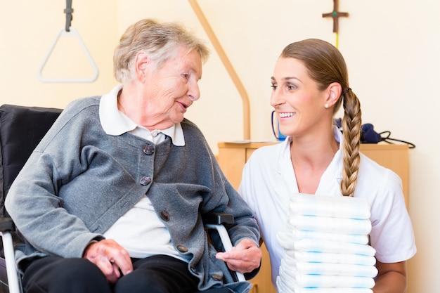 Enfermeira trazendo suprimentos para mulher em lar de idosos