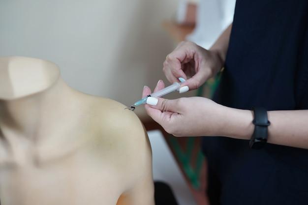 Enfermeira usa luvas de injeção de treinamento com modelo de braço para educação no hospital ou escola de enfermagem