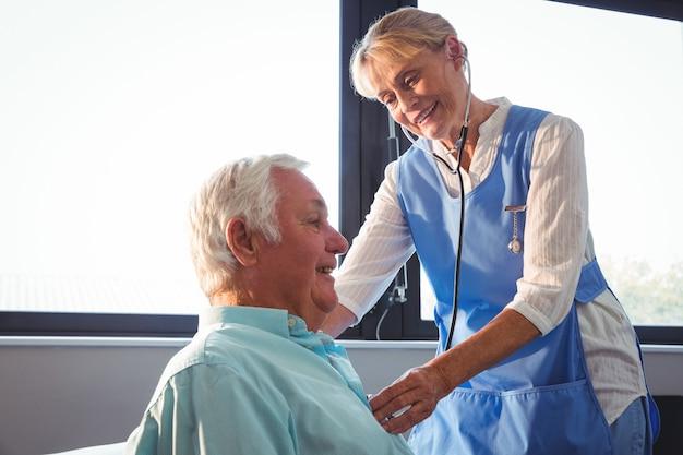 Enfermeira usando estetoscópio para cuidar de um homem sênior