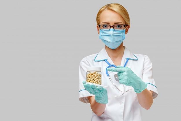 Enfermeira usando máscara protetora e luvas de látex e segurando a lata de remédio e termômetro