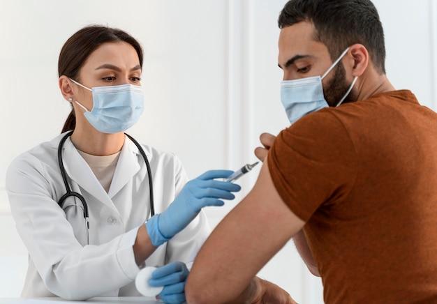 Enfermeira vacinando jovem