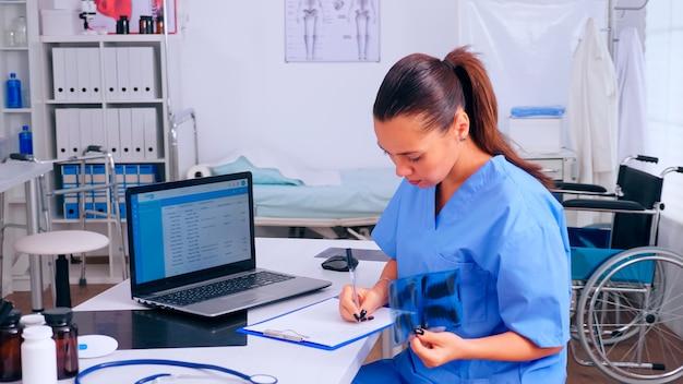 Enfermeira, verificando o resultado do raio-x, lendo a lista de pacientes, fazendo anotações na área de transferência segurando a radiografia. médico em uniforme de medicina, escrevendo a lista de pacientes consultados e diagnosticados, fazendo pesquisas.