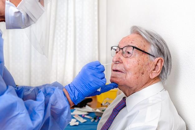 Enfermeira vestida com roupa protetora de coronavírus e máscara, realizando teste de coronavírus em homem idoso.