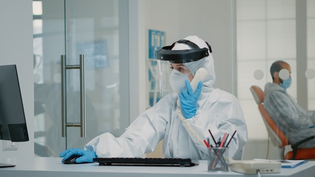 Enfermeira vestindo terno de ppe sentada na mesa da clínica de higiene bucal