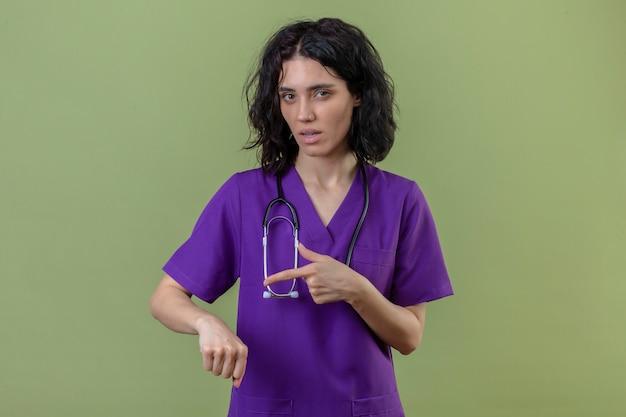 Enfermeira vestindo uniforme e estetoscópio apontando para a mão lembrando sobre o tempo com expressão cética no rosto em pé no verde isolado