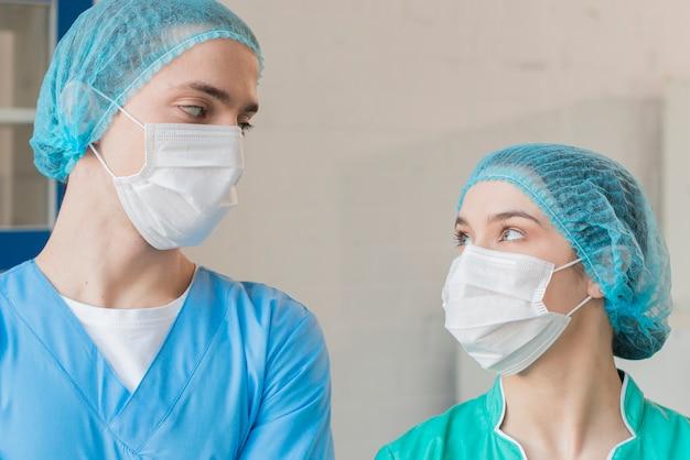 Enfermeiras de baixo ângulo olhando um para o outro