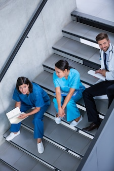 Enfermeiras e médico falando na escada