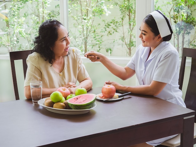 Enfermeiras estão alimentando maçãs para idosos