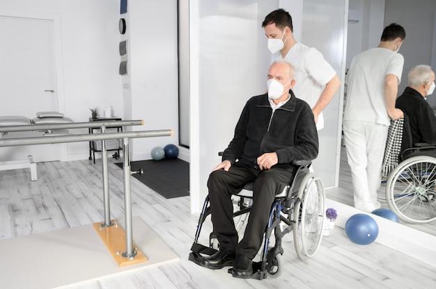 Enfermeiro atendendo paciente idoso com deficiência em cadeira de rodas em centro de reabilitação.