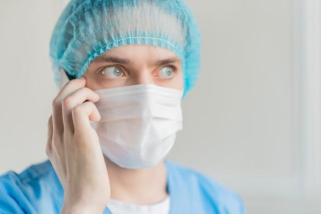 Enfermeiro com máscara falando por telefone
