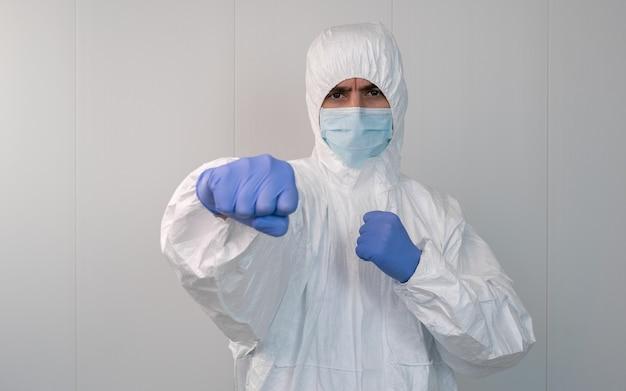 Enfermeiro com traje de proteção epi em guarda dando um soco para combater o coronavírus. conceito de luta contra a pandemia causada pela covid-19.