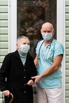 Enfermeiro e mulher idosa com máscaras médicas