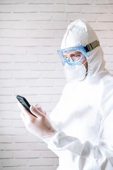 Enfermeiro vestindo traje de proteção e roupas de trabalho usando telefone inteligente