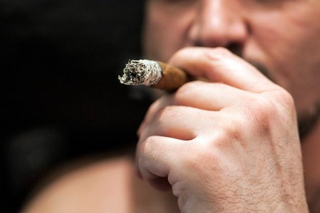 Enfrente no perfil do homem fumando charuto.