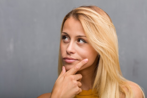 Enfrente o close up, retrato de uma mulher loura nova natural que duvida e confuso, pensando de uma ideia ou preocupado sobre algo