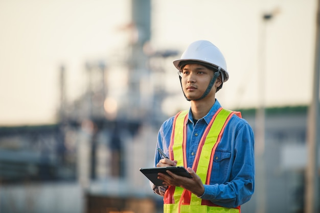 Engenharia asiática trabalhando na refinaria de petróleo e gás