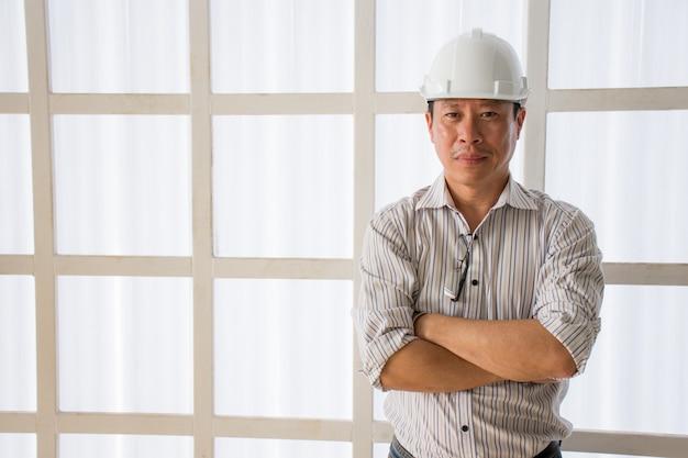 Engenharia asiática, usando, segurança, capacete, braços eretos, cruzado